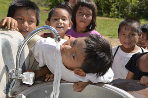 School children of the Matsiegenka Tribe enjoying clean water outside their schoolhouse for drinking and washing.